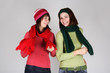 portrait of two young girls in warm scarfs and hats standing and