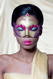 Beautiful young woman wearing a golden carnival mask