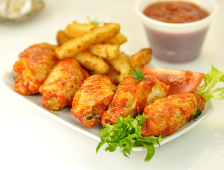hot chicken wings with salad and fried potatoes