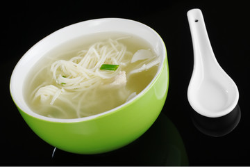 Chinese noodle soup in a green bowl with a spoon