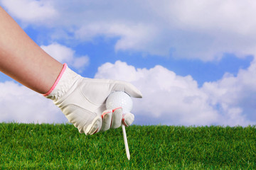 Lady placing a golf ball and tee in the grass