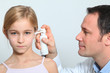 Doctor treating little girl ear infection