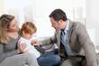 Doctor examining sick little boy