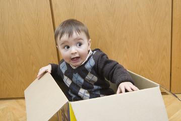 Bebé metido en una caja de cartón.