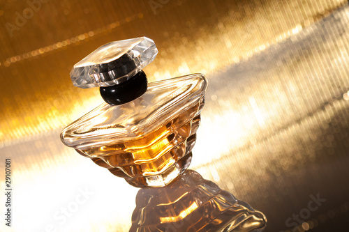 Perfume with reflection on gold background