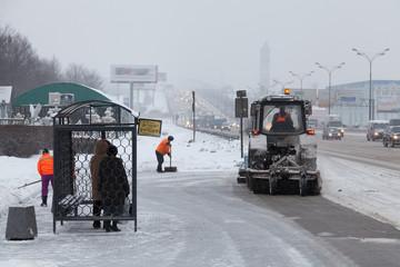 На автобусной остановке уборка снега.