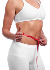 Fit young caucasian woman measuring waist