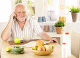 Healthy pensioner using cellphone at breakfast poster