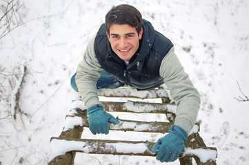 Top view portrait of young smiling handsome man climbing upwards