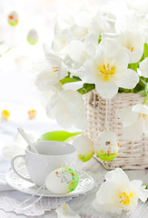 white tulips in a basket and easter eggs