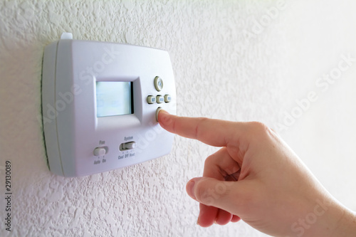 Leinwanddruck Bild thermostat and human hand