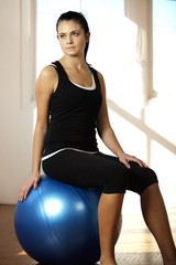 Woman sitting on a fitness ball in the gym