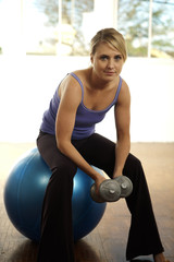 Woman lifting weights sitting on a fitness ball