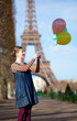 Girl in bright clothes with colourful balloons in Paris near the