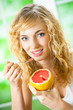 Portrait of young woman eating grapefruit at home