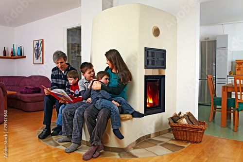 family sitting on the bench of a masonry stove 01