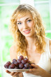 Portrait of young woman with plate of grape, at home