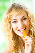 Portrait of young woman eating carrots at home