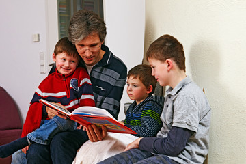 father reading a childrens book to his sons 01