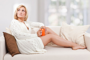 Beauty, blondie woman in a sofa with an orange-colored cup
