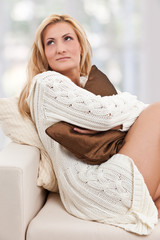 Beauty, blondie woman in a sofa with a brown-colored pillow