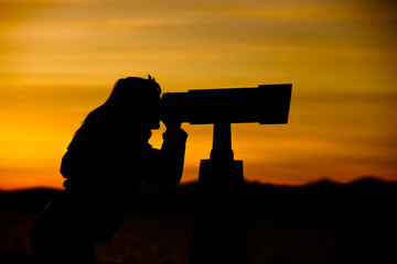 Woman Looking Through Telescope At Sunset