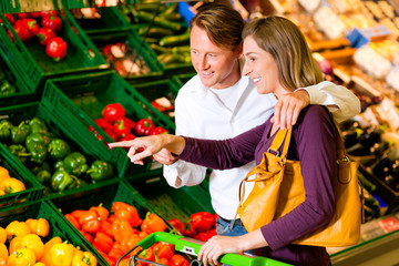 Paar im Supermarkt kauft Gemüse