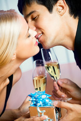 Young happy amorous couple with champagne and gift, kissing