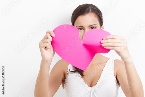 Young woman pulling paper heart to pieces