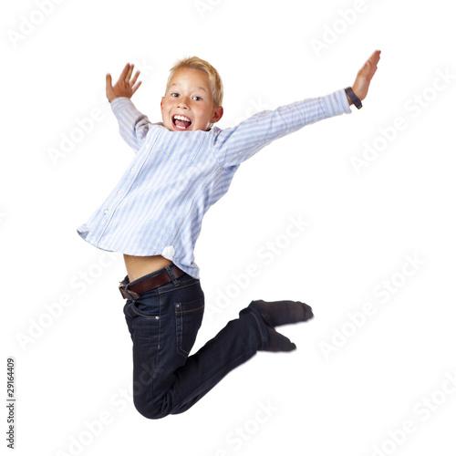Fröhlicher, sportlicher Junge springt mit ausgebreiteten Armen