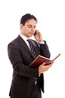 Businessman talking at the phone and looking at his agenda