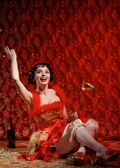 Lady in red dress witn mask throws confetti