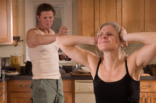 battered wife covers ears as husband yells at her