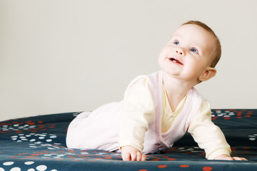 Cheerful baby crawling on a sofa