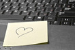 computer keyboard with heart on sticky note