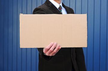 Mann hält leeres Pappschild