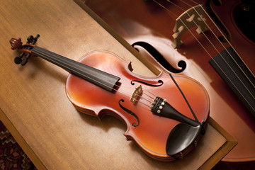 a violin on a piano bench with a double bass on the background