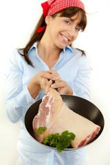 Junge attraktive frau beim braten von fleisch
