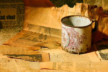 Very old tea cup and old newspaper