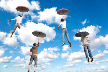 behind flying four friends with umbrellas on White, fluffy cloud