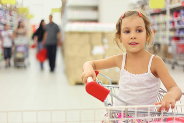 little girl sitting in store cart and looking at side