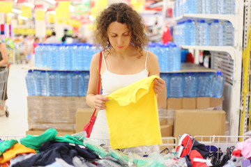 young woman in store holding yellow shirt and looking on it