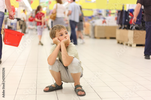 little boy sitting alone on hunkers in big store