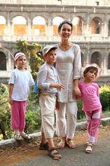 young mother, little son and two daughters are near Colosseum