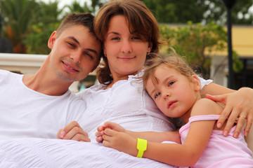 husband and wife and daughter sitting and hug
