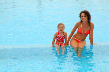 young mother in bathing suit and daugther sitt in swimming-pool