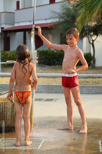 brother and sister are taking outdoor shower after swim