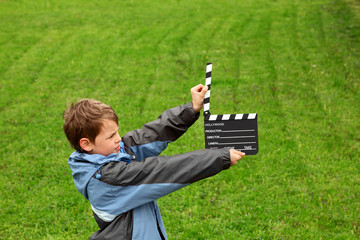 boy with cinema clapper board in hands standing on field