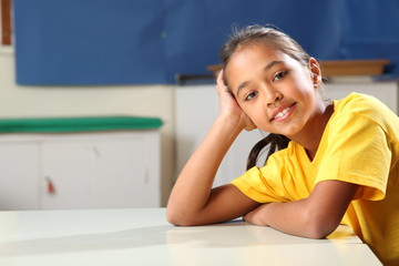 School girl 10 relaxed while sitting at her classroom desk
