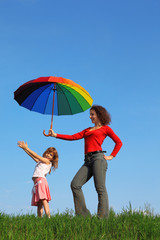 Mother stands on field and holding umbrella over her daughter